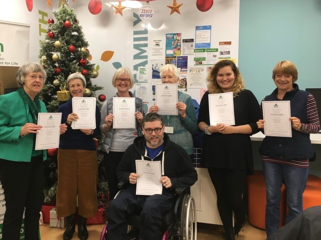 A group photo. Richard sits in his wheelchair in front of 6 volunteers. All are holding their certificates.