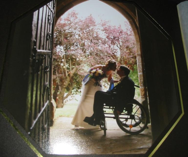 a man in a wheelchair silhouetted in a church doorway, the bride leans forward to kiss him