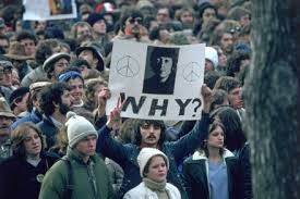 group of people hold a banner. on it is a picture of John Lennon and the word 'why?'