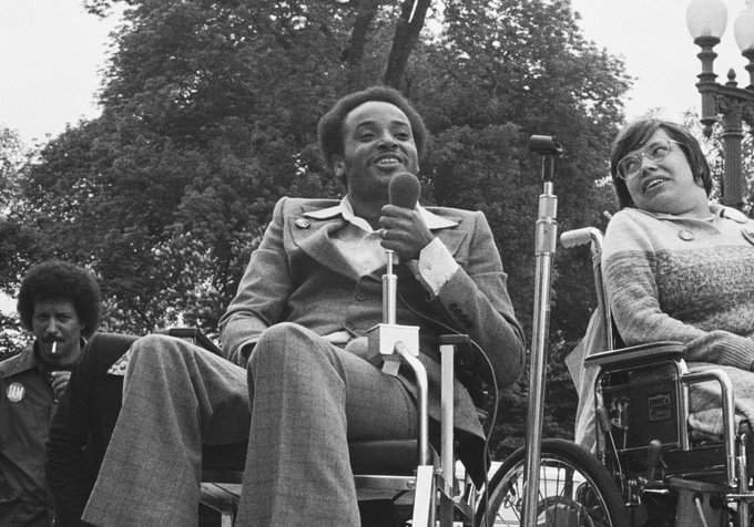 A black man in a wheelchair holds a microphone
