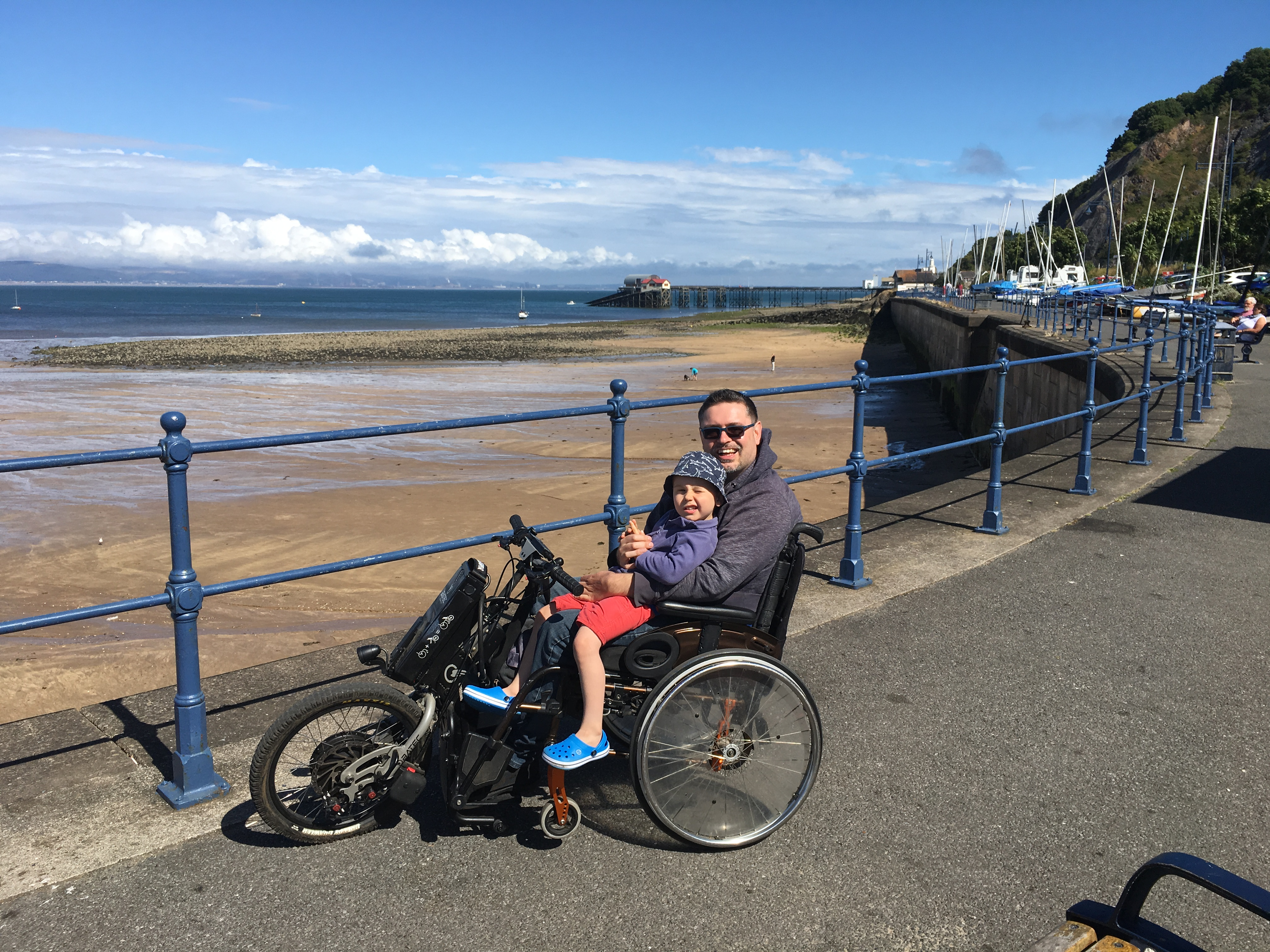 Richard on his Trike overlooking a sandy beach, Billy (nearly 4) sits on his lap