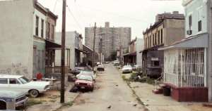 A run-down street with stretches out to a grey apartment block in the distance