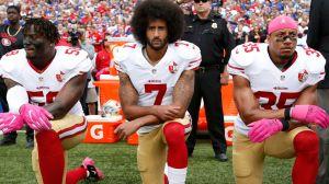 3 American footballers kneeling